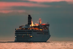 White cruise liner. White passenger ship sailing in evening in still water Royalty Free Stock Photography