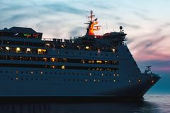 White cruise liner. White passenger ship sailing in evening in still water Stock Photos