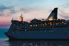 White cruise liner. White passenger ship sailing in evening in still water Royalty Free Stock Images