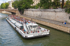 White passenger touristic ship operated by Bateaux-Mouches. Paris, France - August 11, 2014: White passenger touristic ship operated by Bateaux-Mouches goes on Stock Photography