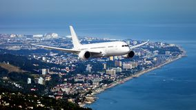 White passenger wide body aircraft in the sky. White passenger wide body aircraft is flying over the seaside city. Airplane front view Stock Image