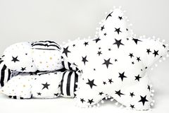 White patchwork feather comforter with black and gold stars and black stripes and white star shaped soft pillow with black s Royalty Free Stock Image