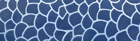 White pattern on a blue wall. White, painted, abstract pattern on a blue house wall - panorama in close-up stock image