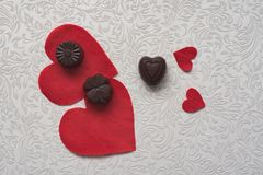 On a white pattern red hearts and chocolates. Still life love. Still-life by the day of the holy Valentine. stock photo