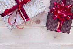 Christmas light wooden background with gift boxes. A white patterned giftbox,a purple striped gift box. Red shiny ribbons on the gift boxes. Light wooden Royalty Free Stock Photos