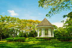 White pavilion in a garden. White pavilion in a green garden in blue sky stock photo