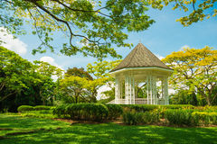 White pavilion in a garden. White House in the blue sky of lawn royalty free stock photo