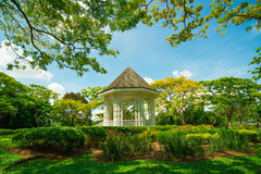White pavilion in a garden. White House in the blue sky of lawn royalty free stock image