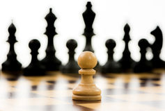 White pawn against a superiority of black chess pieces Stock Image