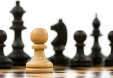 White pawn against a superiority of black chess pieces Royalty Free Stock Image