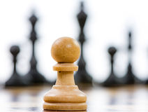White pawn against a superiority of black chess pieces Stock Images
