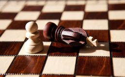 White Pawn beat black chess king on board background Royalty Free Stock Images