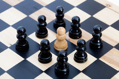 White pawn and black ones. White chess pawn surrounded by black ones Stock Images