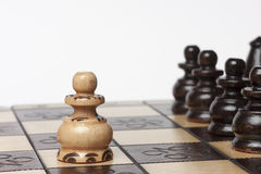 White pawn challenging army of black chess pieces. Selective focus Royalty Free Stock Image