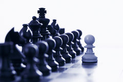 White pawn challenging black chess pieces. White pawn challenging army of black chess pieces blue tone stock image