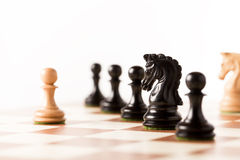white pawn on a chessboard with black chess pieces Royalty Free Stock Photos
