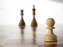 White  pawn in front of black king and queen Royalty Free Stock Photos