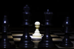 White pawn standing alone in spotlight on chess board with black Royalty Free Stock Photos