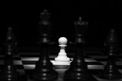 White pawn standing alone in spotlight on chess board with black Royalty Free Stock Photography