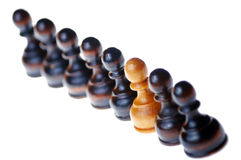White pawn standing out in a group of black pawns Stock Photos