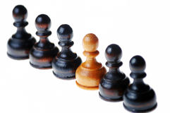 White pawn standing out in a group of black pawns Royalty Free Stock Photo