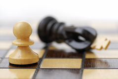 White Pawn Standing Over Defeated King. Royalty Free Stock Images