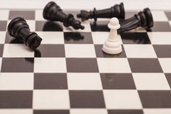 White pawn surrounded by black chess pieces Royalty Free Stock Photo