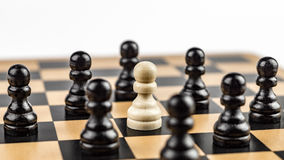 Free White Pawn Surrounded By Enemies Stock Image - 84416721
