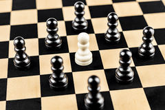 White Pawn surrounded by Enemies. White Pawn trapped by black ones Royalty Free Stock Photo