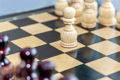 White pawn on a wooden chessboard. The game of chess