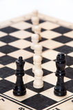 White pawns in front of a black queen and king Royalty Free Stock Images