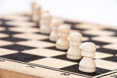 White pawns lined up diagonally across the chessboard Stock Photo