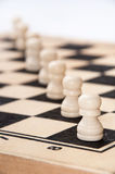 White pawns lined up diagonally across the chessboard Stock Photos