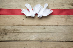 White peace doves on red ribbon and wooden background Royalty Free Stock Image