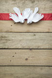 White peace doves on red ribbon and wooden background Royalty Free Stock Photography