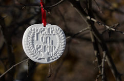 White Peace on Earth Christmas Ornament Hanging in the Winter Woods Royalty Free Stock Photo