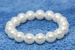 White pearl bracelet. On blue material Stock Images