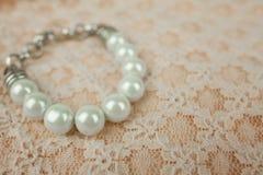 White Pearl Bracelet on Vintage Peach Lace Pattern Stock Photo