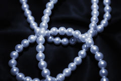 White pearl necklace on a black silk Stock Photography