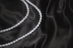 White pearl necklace on a black silk Stock Images