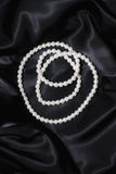 White pearl necklace on a black silk close up royalty free stock images