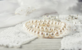 White pearl necklace on handmade lace background. Photo toned royalty free stock photos