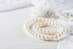 White pearl necklace on handmade lace background. Royalty Free Stock Photo