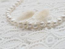 White pearl necklace and lagurus on white lace Stock Photos