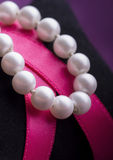 Pearl Necklace over Pink Ribbon Stock Image