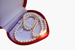 White pearl necklace on a red box is a heart shape. stock photography
