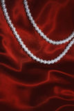 White pearl necklace on a red silk Royalty Free Stock Images