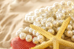 White pearl and seashells on sand Royalty Free Stock Photos
