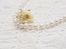 White pearl with white rose on white lace Royalty Free Stock Image