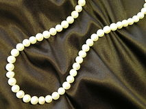 White pearls beads. White pearls necklace on brown satine Royalty Free Stock Photo